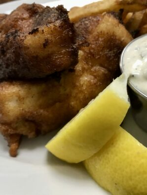 batter dipped cod with tartar sauce and lemon wedges