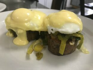 crispy potato discs covered in leeks, poached eggs and hollandaise sauce